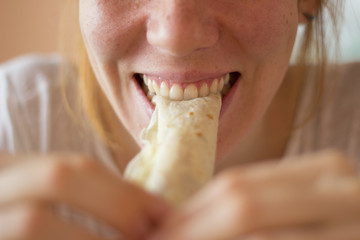 Woman smiling and eating fresh crepe for breakfast, close-up.