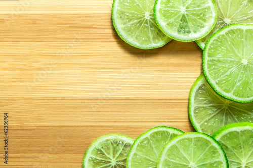 Lime slices on wooden background.