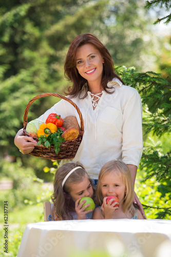 Smiling mother and two daughters having fun in a picnic