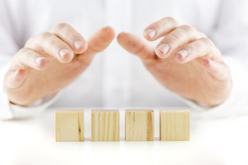 Man holding his hands protectively over a row of four blank cube