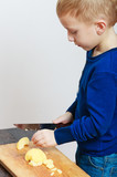 Boy child kid preschooler with kitchen knife cutting fruit apple