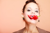 Beautiful woman fashion girl with red lips biting chilli pepper