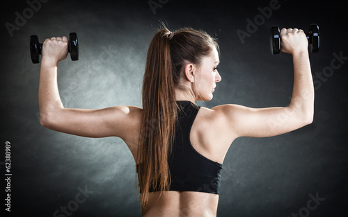 Fitness girl training shoulder muscles. Back view