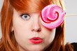 Woman holding candy. Redhair girl with sweet lollipop making fun