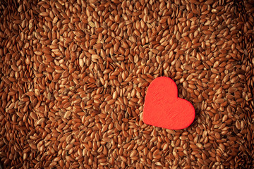 Diet. Flax seeds linseed as food background and red heart
