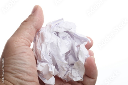 male hand holding crumpled paper over a white