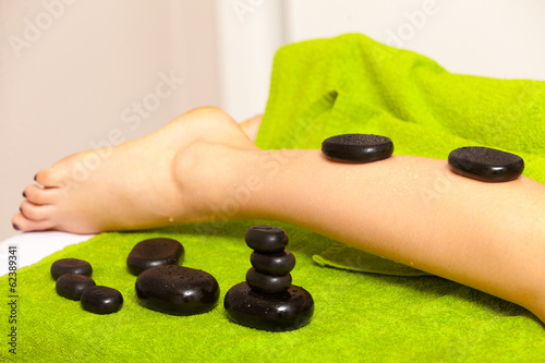 Beauty salon. Woman getting spa hot stone legs massage