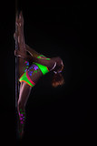 Flexible girl dancing on pole under UV light