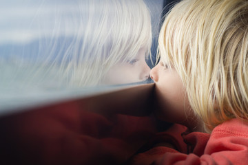 Cute child deep in thought looking out a window