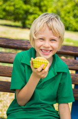 Happy school child eating homemade cupcake outdoors