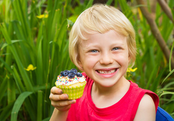 Cute child holding colorful muffin in the garden