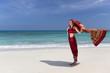 Woman wearing an Indian Saree walking along the beach.