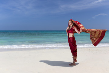 Woman wearing an Indian Saree walking along the beach.