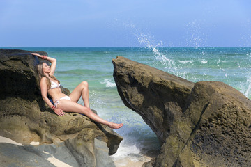 Woman posing on rocks in bikini