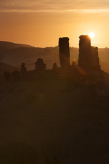 Sunrise silhouette of Corfe castle Ruins near Swanage. UK.