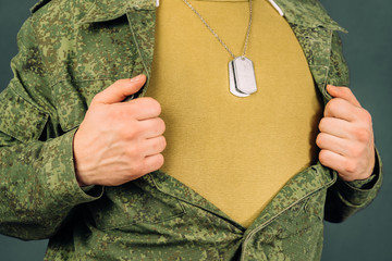 Military man opens his shirt, copyspace