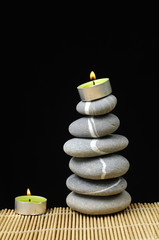 Stack of stone and candles at the black background