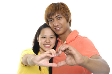 girl and her boyfriend making shape of heart by their hands