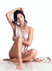 Sensual young woman with beautiful body in the beige silk