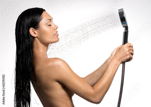 woman in shower washing body under the stream of water