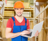 Portrait of handyman with laptop working warehouse