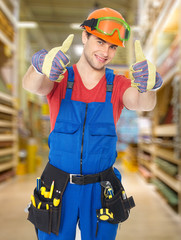 professional young worker with thumbs up at shop