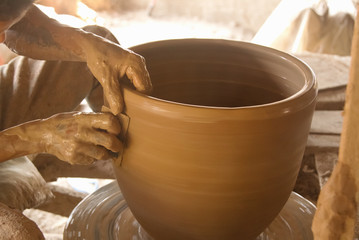 Potter's hands working on a pot at his pottery wheel