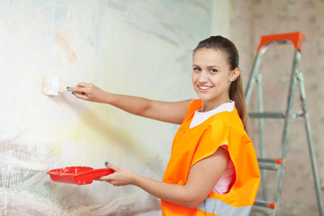 woman in uniform paints wall