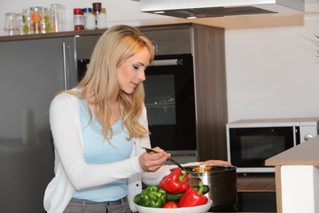 Attractive young housewife cooking in the kitchen