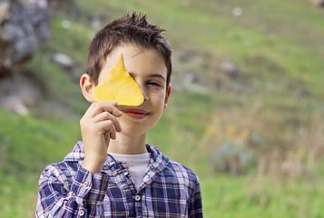 Niño cubriendose la cara con hoja de otoño