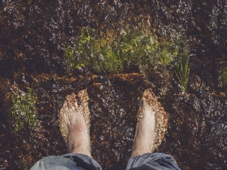 man's feet in the river stream