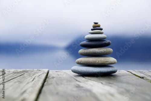 Leinwanddruck Bild Zen Balancing Pebbles Next to a Misty Lake