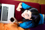 Woman working at home with technology thumb up