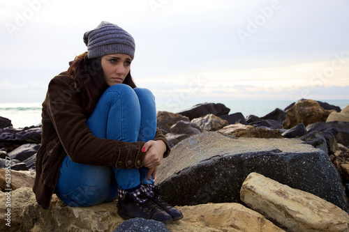 Sad young woman sitting in front of the ocean in the winter