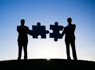 Two Businessmen Holding Jigsaw Puzzle