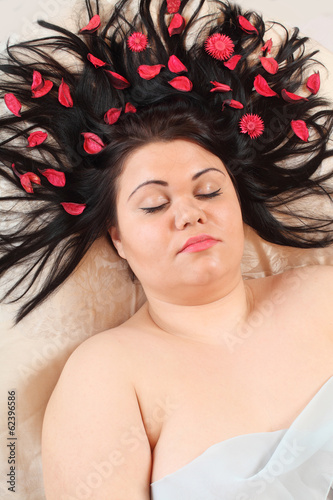 Overweight woman relaxing with herbs in her haircut.