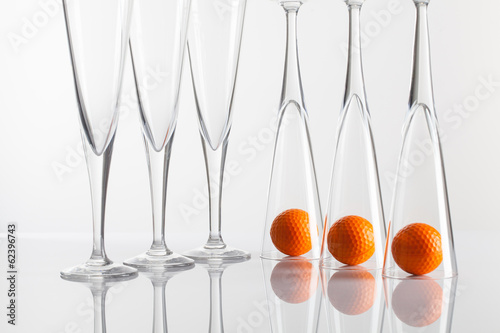 Glasses of champagne and golf equipments on a glass table