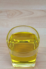 A glass of Cooking Oil on a wooden background