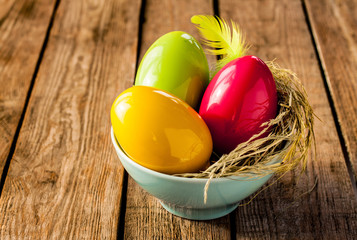 Easter decoration - colorful glossy eggs on vintage rustic wood