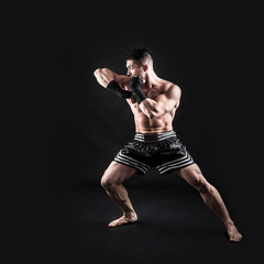 Sportsman kick boxer full body portrait against black background