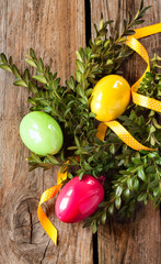 Easter decoration - colorful eggs with buxus on vintage wood