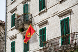 Flag of Montenegro on old building with Green shutters