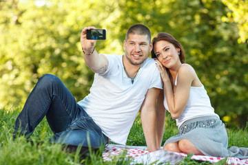 Beautiful young couple taking a self portrait in the park