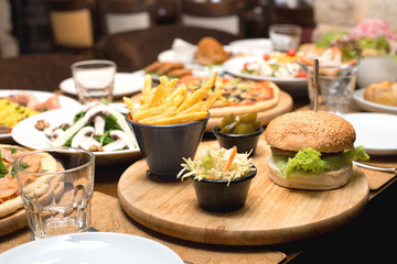 Beef burger and french fries on a table with other food plates