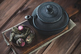 Compressed tea and cast-iron asian teapot, wooden background