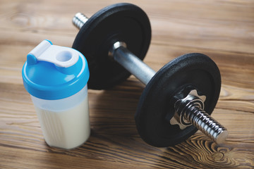 Shaker with protein and a dumbbell on a wooden surface, close-up