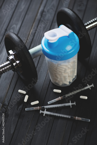 Shaker with tablets, syringes and a dumbbell, vertical shot