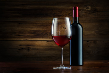 glass and bottle of wine on a wooden background
