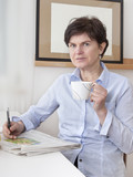 Woman relaxing drinking a cup of coffee and reading newspaper