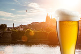 Glass of beer against view of the St. Vitus Cathedral in Prague